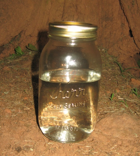 A quart Kerr jar of white liquor.